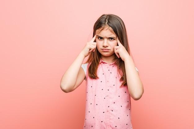 Menina bonitinha focada em uma tarefa, mantendo-o dedos apontando a cabeça. Foto Premium