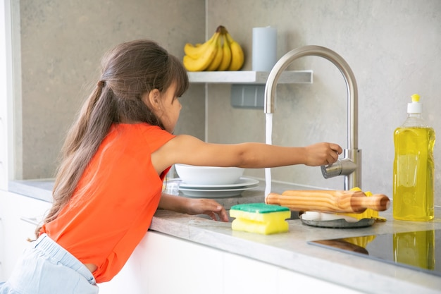 Menina bonitinha lavando prato na cozinha sozinha. criança alcançando a torneira da pia da cozinha e abrindo a água. Foto gratuita
