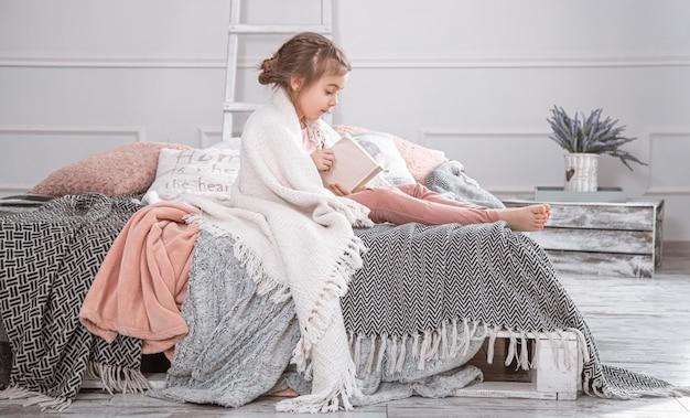 Menina bonitinha lendo um livro na cama. Foto gratuita