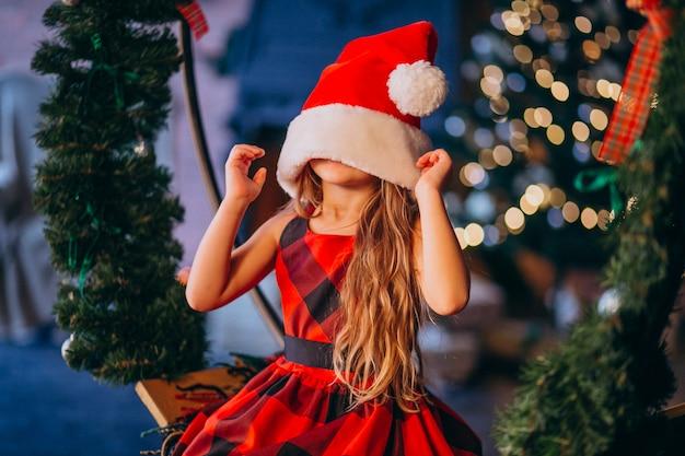 Menina bonitinha no chapéu de papai noel e vestido vermelho Foto gratuita