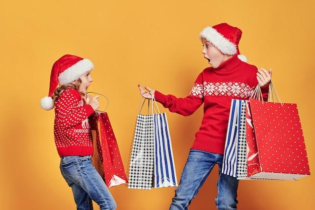 Menina bonitinha no chapéu de papai noel, pendurando a sacola de compras com presentes de natal na mão do menino atônito durante a celebração do feriado contra fundo amarelo Foto Premium