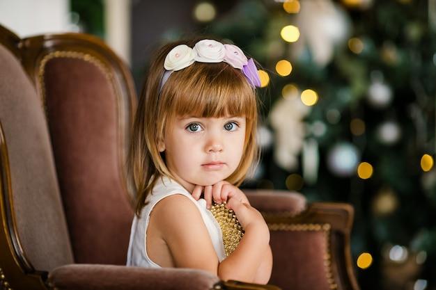 Menina bonitinha no vestido branco com coroa de flores agradável perto da árvore de natal Foto Premium