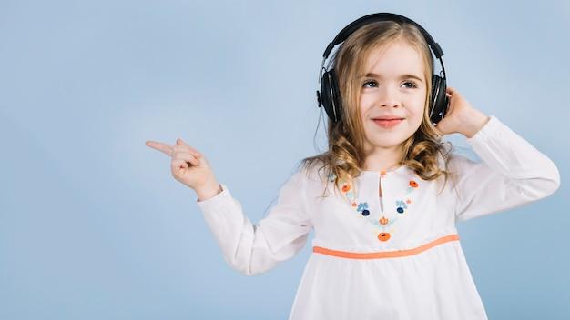 Menina bonitinha ouvindo música no fone de ouvido apontando o dedo para algo Foto gratuita