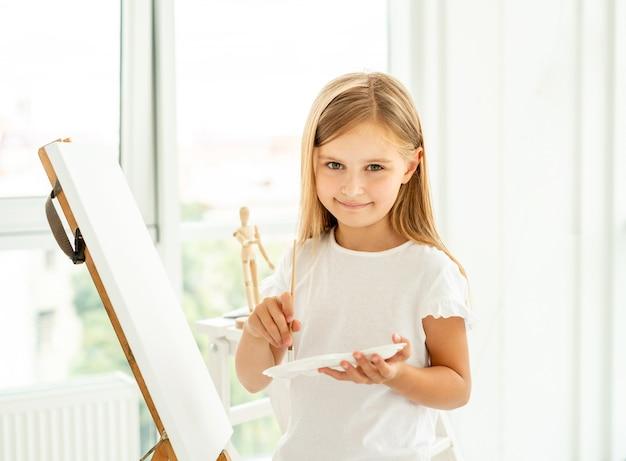 Menina bonitinha pinta sobre tela Foto Premium