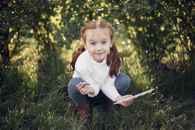 Menina bonitinha pintando em um parque Foto gratuita