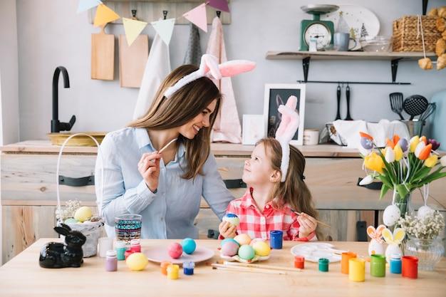 Menina bonitinha pintar ovos para a páscoa com a mãe Foto gratuita