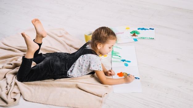 Menina bonitinha pintura com aquarelle brilhante no chão Foto gratuita
