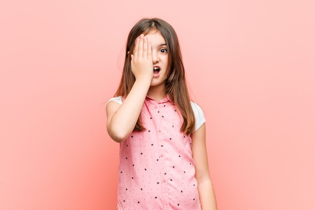 Menina bonitinha se divertindo cobrindo metade do rosto com palm. Foto Premium