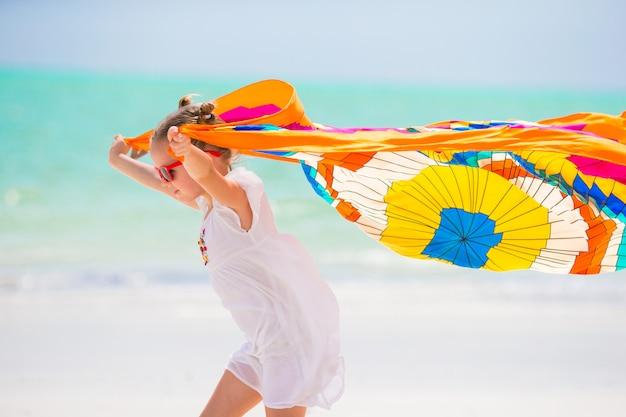Menina bonitinha se divertindo correndo com pareo na praia tropical Foto Premium