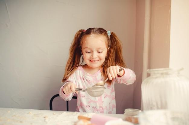 Menina bonitinha se divertir em uma cozinha Foto gratuita