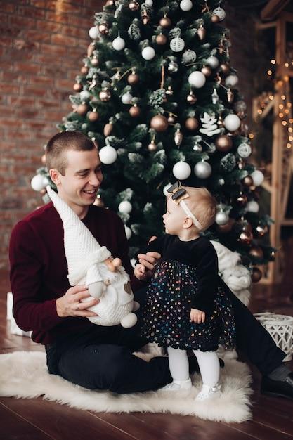 Menina bonitinha sentada com seu pai com árvore de natal Foto Premium
