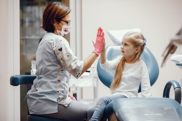 Menina bonitinha sentada no consultório do dentista Foto gratuita