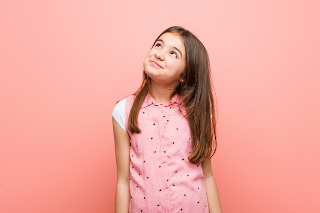 Menina bonitinha sonhando em alcançar metas e propósitos Foto Premium