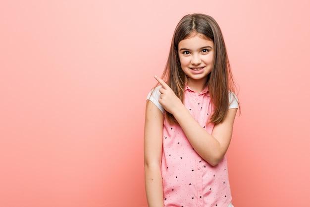 Menina bonitinha sorrindo e apontando de lado, mostrando algo no espaço em branco. Foto Premium