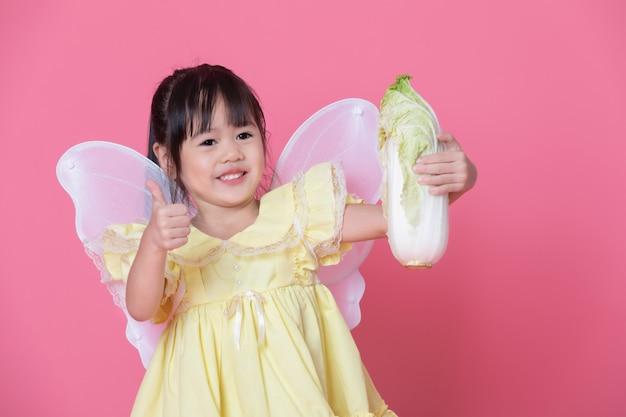 Menina bonitinha vestir-se como um anjo com asas brancas, mantendo o repolho e o polegar. conceito de comer e estilo de vida saudável. comida vegetariana verde Foto Premium