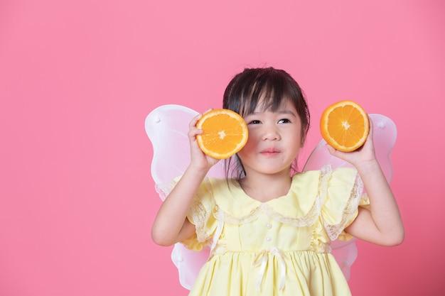 Menina bonitinha vestir-se como um anjo com asas brancas, segurando uma metade da laranja. conceito saudável de comer e estilo de vida. comida vegetariana Foto Premium