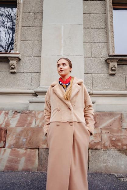 Menina bonito à moda nova em um casaco de pele que dá uma volta em torno da cidade perto das casas de madeira e das paredes de pedra Foto Premium