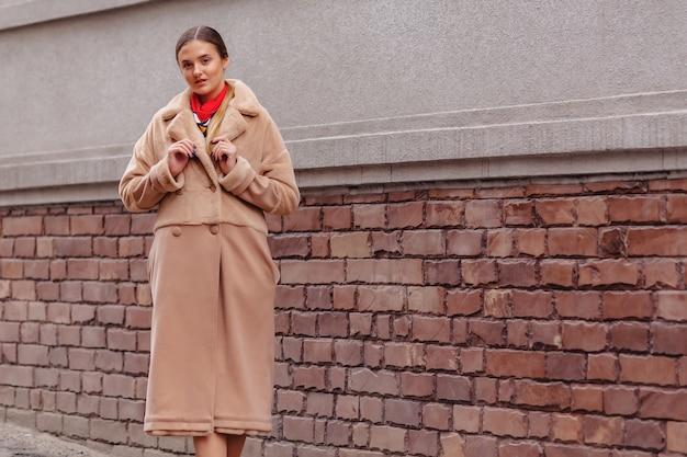 Menina bonito à moda nova em um casaco de pele que dá uma volta em torno da cidade perto das casas de madeira Foto Premium