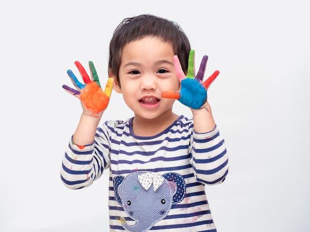 Menina bonito asiática engraçada que joga a pintura da aguarela nas mãos. Foto Premium