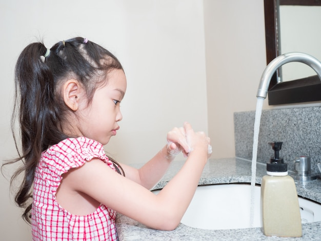 Menina bonito asiática lavando as mãos com sabão na bacia. criança que limpa as mãos com sabão para proteger bactérias e coronavírus, covid-19 Foto Premium