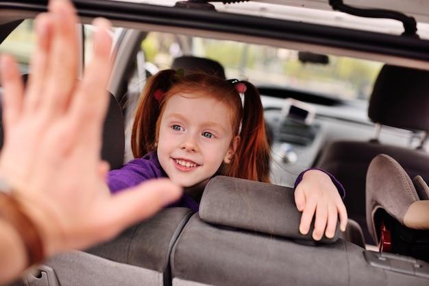 Menina bonito com cabelo vermelho, sorrindo para o interior do carro Foto Premium