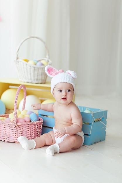 Menina bonito com os ovos da páscoa que sentam-se no assoalho em casa. Foto gratuita
