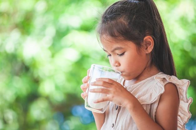 Menina bonito criança asiática está bebendo um leite de vidro Foto Premium