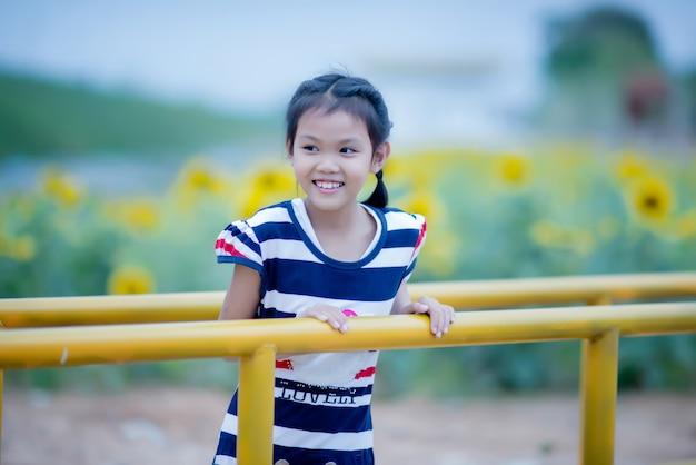 Menina bonito da criança com girassol no campo de verão Foto gratuita
