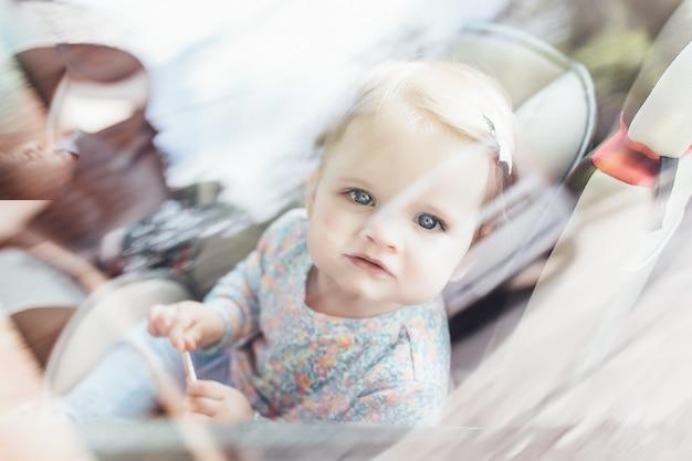Menina bonito da criança pequena que senta-se no assento da segurança dentro do carro. prevenção de perigo. Foto Premium