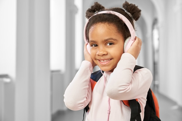 Menina bonito da escola segurando grandes fones de ouvido rosa Foto Premium
