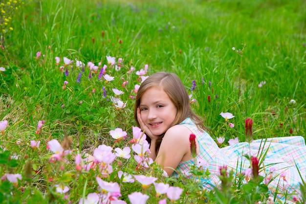 Menina bonito de crianças na primavera prado com flores de papoula Foto Premium