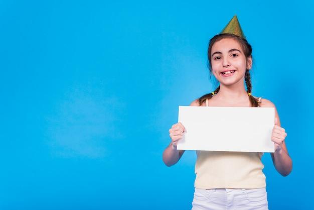 Menina bonito de sorriso que desgasta o chapéu do partido que prende o cartão em branco na mão na frente do papel de parede colorido Foto gratuita