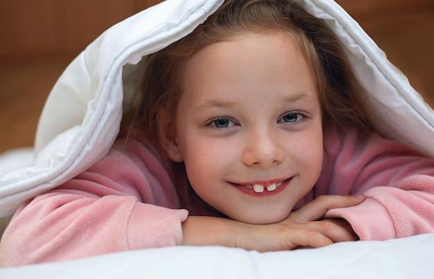 Menina bonito, escondendo-se debaixo do cobertor Foto Premium