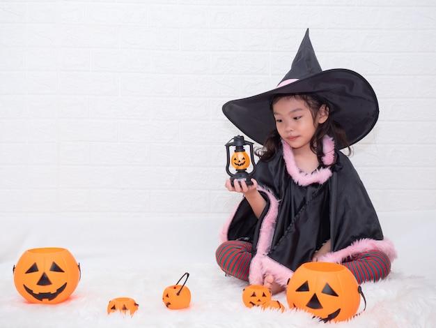 Menina bonito pequena cosplay como uma bruxa e segurando a abóboras lâmpada e baldes em fundo branco. Foto Premium