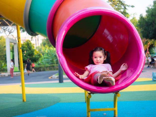 Menina bonito pequena engraçada que joga a corrediça no campo de jogos. Foto Premium