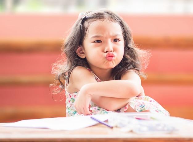 Menina bonito pequena irritada com cruz seu braço quando sua mãe proíbe a observação de desenhos animados e diz-lhe para tirar. Foto Premium
