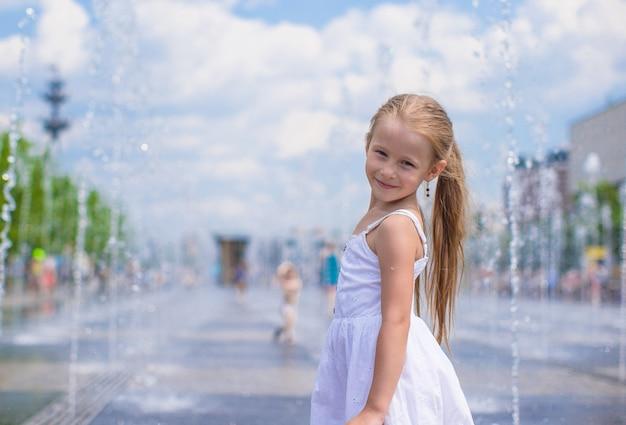 Menina bonito se divertir na fonte de rua aberta no dia quente de verão Foto Premium