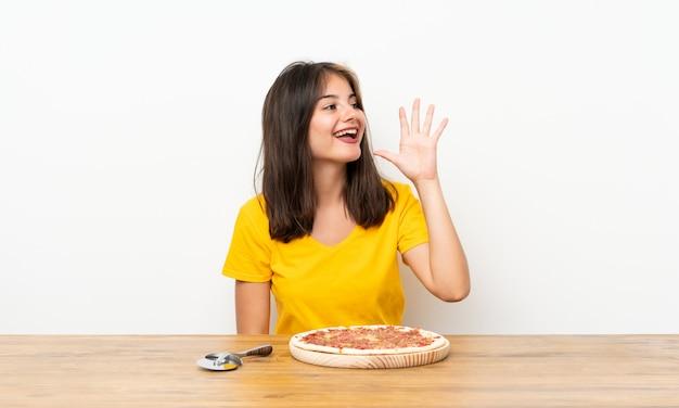 Menina branca com uma pizza gritando com a boca aberta Foto Premium