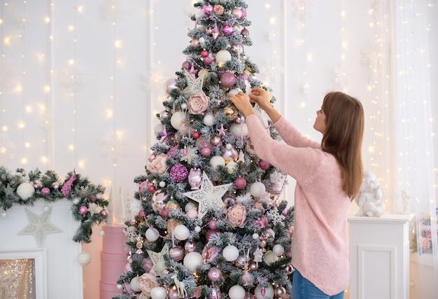 Menina branca em um vestido de malha-de-rosa decora uma árvore de natal com  brinquedos de natal   Foto Premium
