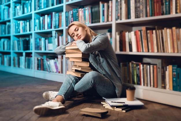Menina branca está dormindo com livros no colo. Foto Premium