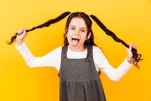 Menina brincalhão com a língua de fora enquanto segura o cabelo de tranças Foto gratuita