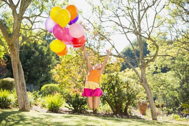 Menina brincando com balões no parque Foto Premium