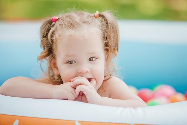 Menina brincando com brinquedos na piscina inflável no dia ensolarado de verão Foto gratuita