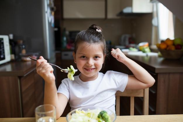 Menina brincando com comida enquanto come Foto gratuita