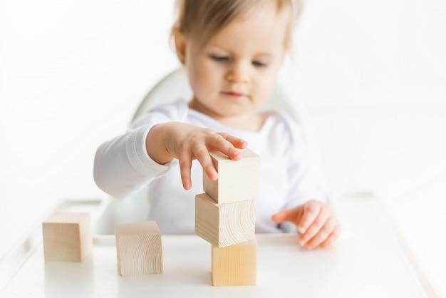 Menina brincando com cubos de madeira pela mão esquerda. jogando a criança isolada no fundo branco. jogos para crianças, educação pré-escolar. feche acima, foco seletivo Foto Premium