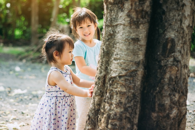 Menina brincando debaixo da grande árvore Foto Premium