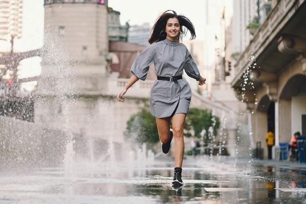 Menina brincando e dançando em uma rua molhada Foto gratuita