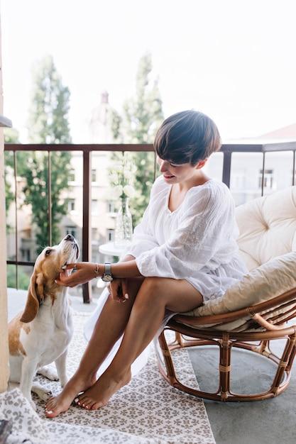 Menina bronzeada com manicure elegante e pedicure brincando com cachorro beagle engraçado que descansa no tapete Foto gratuita