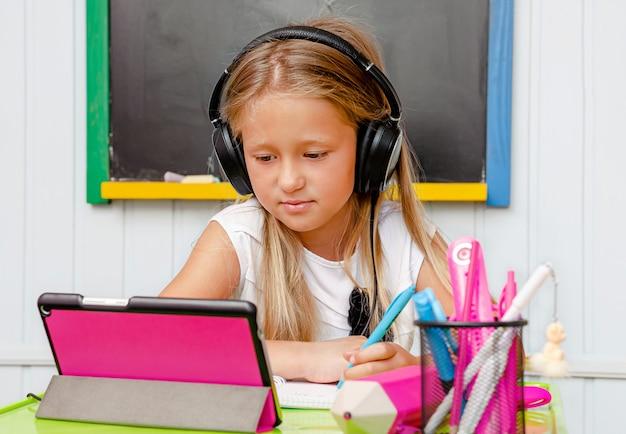 Menina canhota da escola bonito estudando on-line. Foto Premium