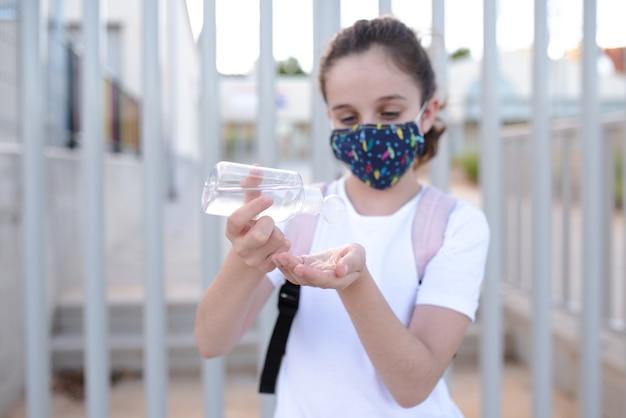 Menina caucasiana com máscara derramando gel hidroalcoólico nas mãos na porta da escola no novo normal Foto Premium